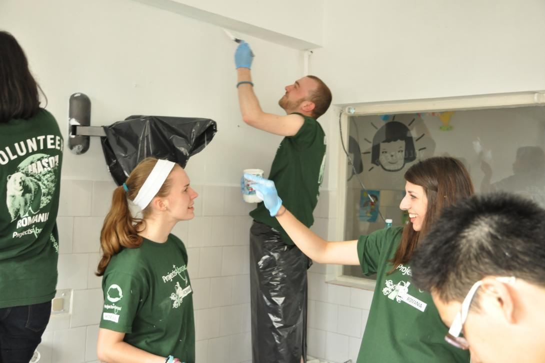 Smiling volunteer workers in Romania help to paint a room